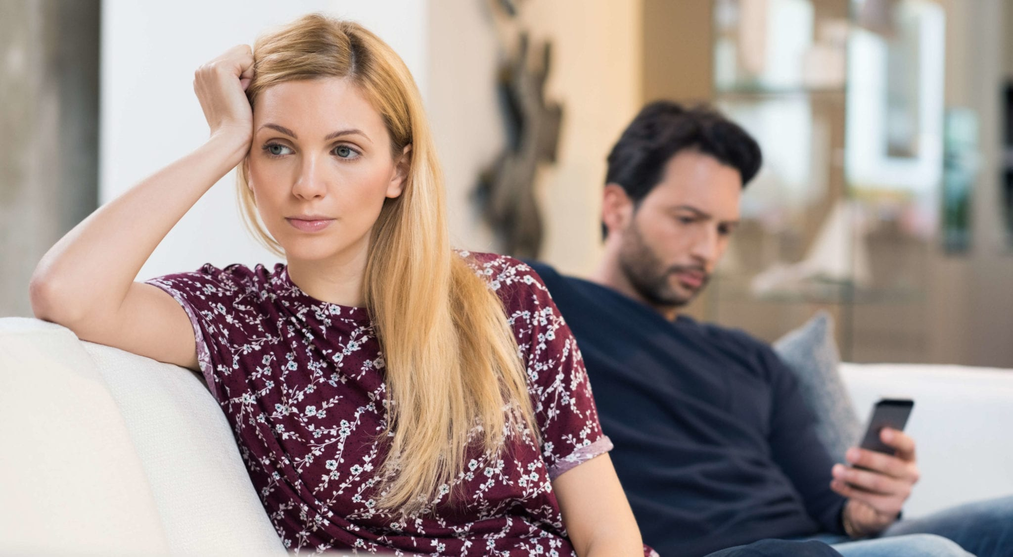 Couple sitting on couch looking unhappy