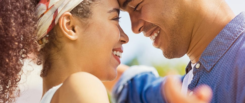 Portrait of happy young couple face to face and looking at each